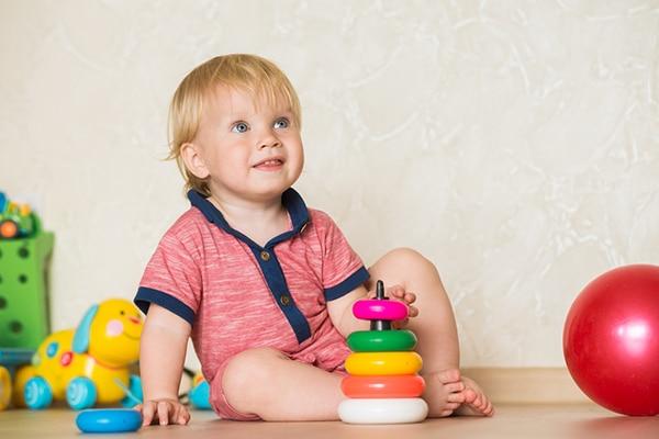1-jarig jongetje zitten op de grond naast speelgoed kijkt lachend omhoog