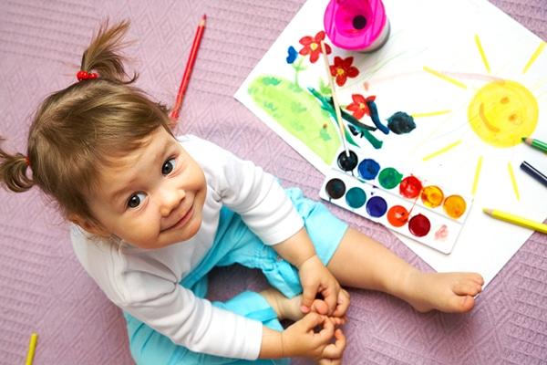 1-jarig meisje kijkt lachend omhoog zittend naast tekening