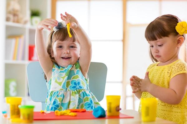 2-jarige meisjes in kleurige jurkjes spelen met Playdough aan tafel