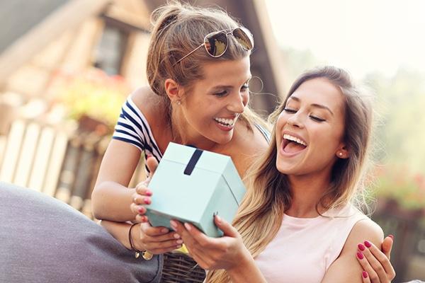 meisje geeft cadeau aan vriendin en ze lachen samen