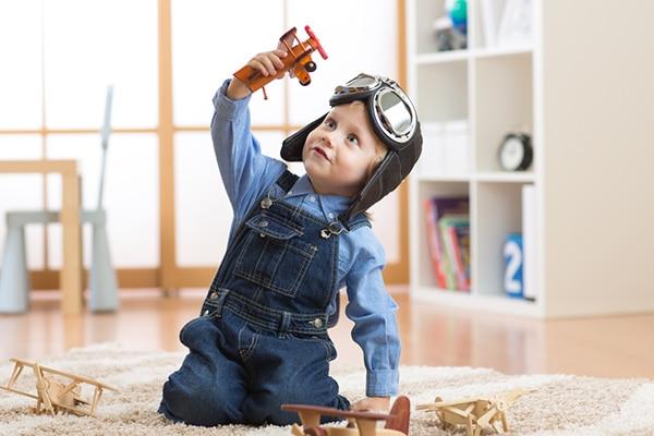2-jarige jongen speelt met oranje speelgoedvliegtuigje