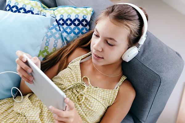 10-jarig meisje met tablet en koptelefoon zit op de bank