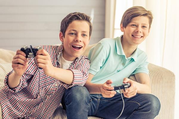 10-jarige jongens spelen met de PlayStation en zitten op de bank