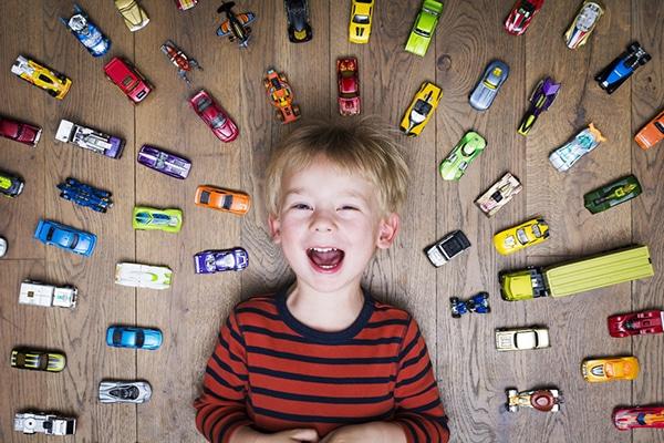 3-jarige jongen ligt lachend op grond tussen speelgoedautootjes