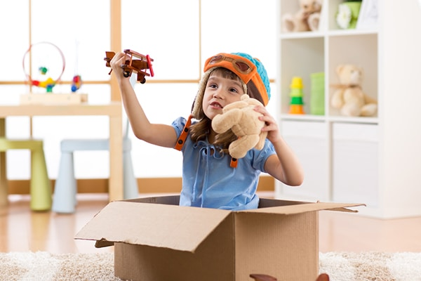 4-jarig meisje zit in kartonnen doos en speelt met speelgoedvliegtuigje en teddybear