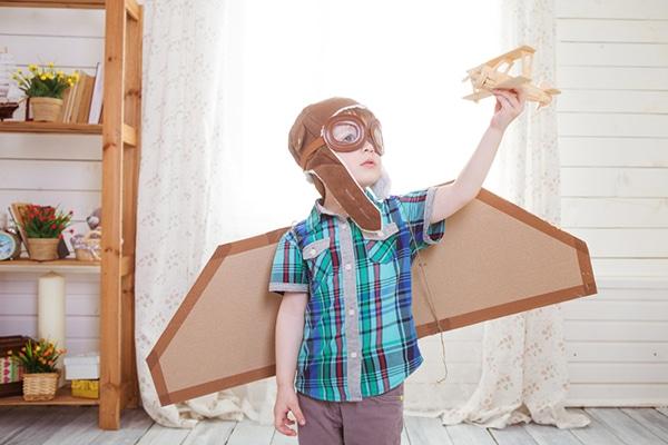 4-jarige jongen met vliegtuighelm- en vleugels aan speelt met miniatuurvliegtuigje