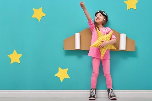 7-jarig meisje met vliegtuigvleugels lacht en steekt vuist in lucht omhoog