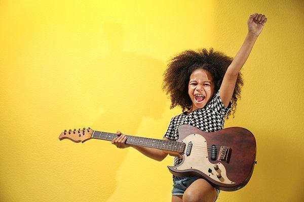 8-jarig meisje speelt gitaar en steekt arm in de lucht over een gele achtergrond