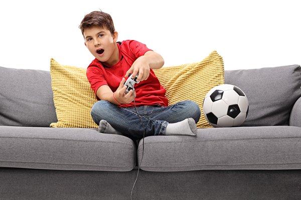 8-jarige jongen zit gehurkt op de bank en speelt op de playstation