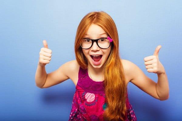 9-jarig meisje met rood haar en bril steekt lachend duimen omhoog over een blauwe achtergrond