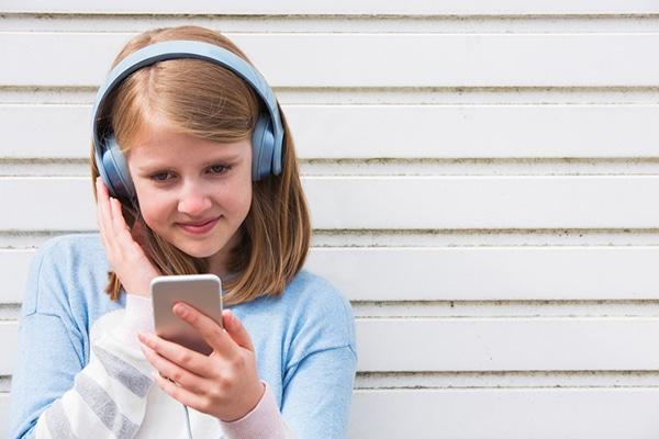 12-jarig meisje lacht naar smartphone en heeft koptelefoon op