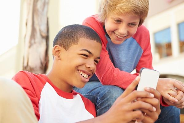 13-jarige jongens zitten op de bank en kijken lachend naar een smartphone