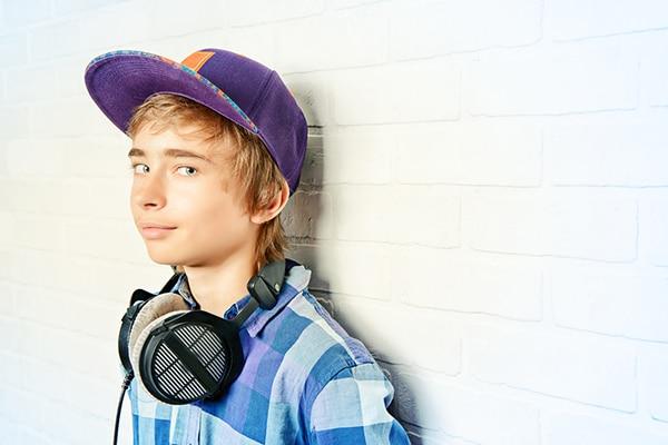 14-jarige jongen met paarse pet en koptelefoon leunt tegen muur