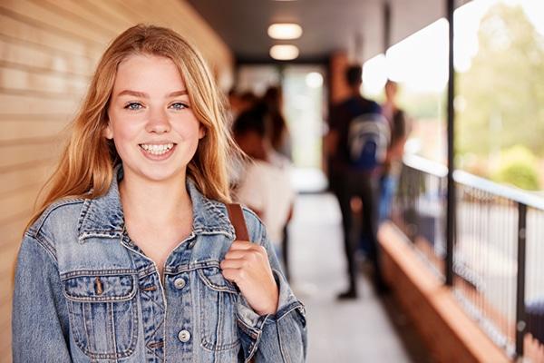 15-jarig meisje op school lacht naar camera met vrienden op achtergrond