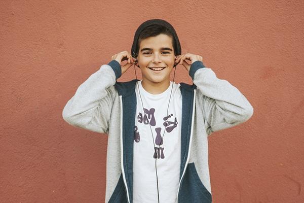 15-jarige jongen met zwarte muts en oordopjes in lacht in camera