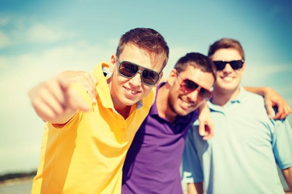 18-jarige jongens met zonnebril staan schouder aan schouder en kijken naar camera